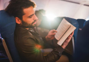 Young man traveling by airplane and reading a book.