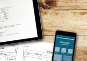 website wireframe sketch and digital tablet with programming code on wooden table. programming code is my own property