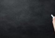 Blank blackboard or chalkboard with hand holding chalk writing on black chalk board