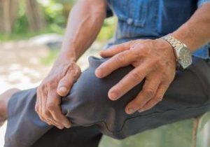 man sitting holding his knee